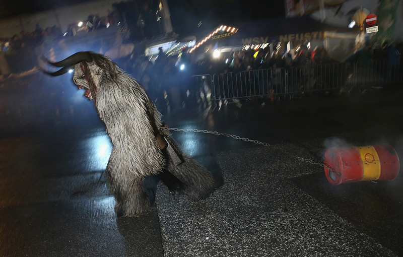 . A participant dressed as the Krampus creature pulls a barrel of fire past onlookers during his search for delinquent children during Krampus night on November 30, 2013 in Neustift im Stubaital, Austria. Sixteen Krampus groups including over 200 Krampuses participated in the first annual Neustift event. Krampus, in Tyrol also called Tuifl, is a demon-like creature represented by a fearsome, hand-carved wooden mask with animal horns, a suit made from sheep or goat skin and large cow bells attached to the waist that the wearer rings by running or shaking his hips up and down. Krampus has been a part of Central European, alpine folklore going back at least a millennium, and since the 17th-century Krampus traditionally accompanies St. Nicholas and angels on the evening of December 5 to visit households to reward children that have been good while reprimanding those who have not. However, in the last few decades Tyrol in particular has seen the founding of numerous village Krampus associations with up to 100 members each and who parade without St. Nicholas at Krampus events throughout November and early December.  (Photo by Sean Gallup/Getty Images)