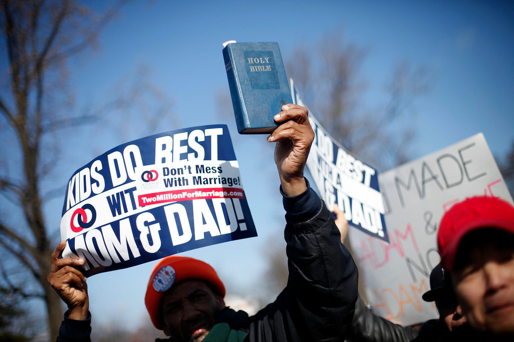 . A demonstrator holds a bible while marching outside the Supreme Court in Washington, Tuesday, March 26, 2013, as the court heard arguments on California\'s voter approved ban on same-sex marriage, Proposition 8.  (AP Photo/Pablo Martinez Monsivais)