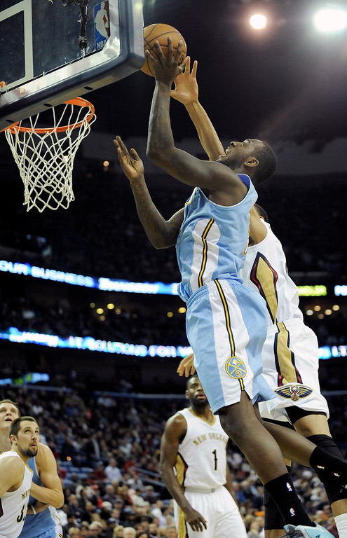 . New Orleans Pelicans center Anthony Davis, right, fouls Denver Nuggets forward J.J. Hickson, left, during the first half of an NBA basketball game in New Orleans, Friday, Dec. 27, 2013.  (AP Photo/Stacy Revere)