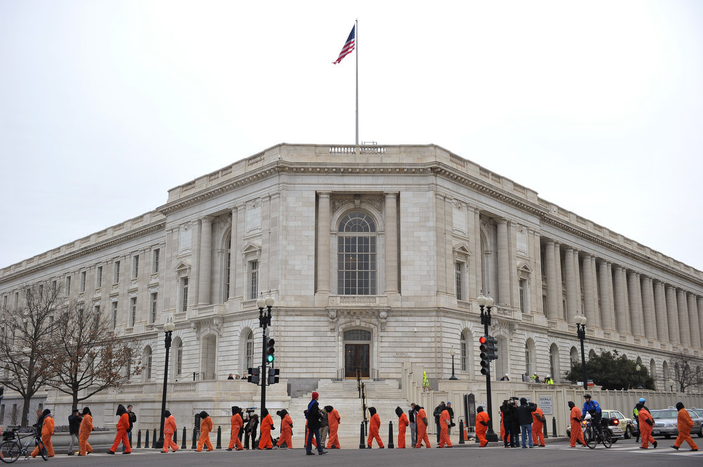 Description of . Hooded demonstrators march infront of the Russell Senate Office Building to call for the closing of the Guantanamo Bay detention center on January 11, 2013 on Capitol Hill in Washington, DC. MANDEL NGAN/AFP/Getty Images