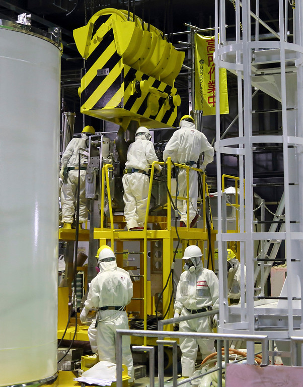 . Workers wearing protective suits and masks work on a crane for a transport container inside the building housing the Unit 4 reactor at the Fukushima Dai-ichi nuclear power plant in Okuma, Fukushima, northeastern Japan, Thursday, Nov. 7, 2013.  (AP Photo/Tomohiro Ohsumi, Pool)