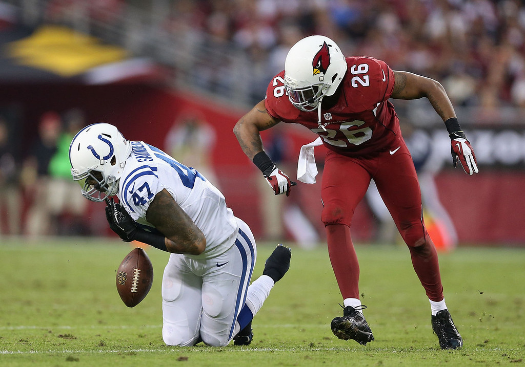 . Tight end Weslye Saunders #47 of the Indianapolis Colts has the football knocked loose by free safety Rashad Johnson #26 of the Arizona Cardinals during the third quarter of the NFL game at the University of Phoenix Stadium on November 24, 2013 in Glendale, Arizona. The Cardinals defeated the Colts 40-11. (Photo by Christian Petersen/Getty Images)