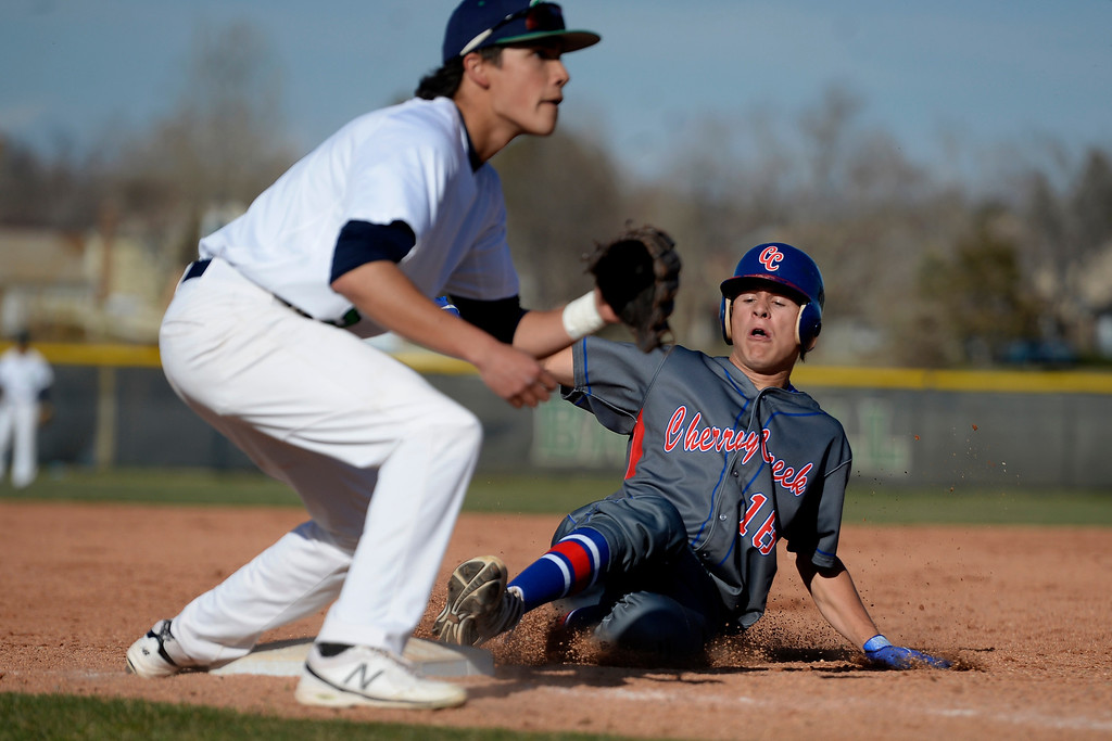 . Aurora, CO - APRIL 08: Grant Farrell (16) of the Cherry Creek Bruins steals third base as Jesse Granados (5) of the Overland Trailblazers awaits the throw from home during league action. Overland hosted Cherry Creek on Tuesday, April 8, 2014. (Photo by AAron Ontiveroz/The Denver Post)