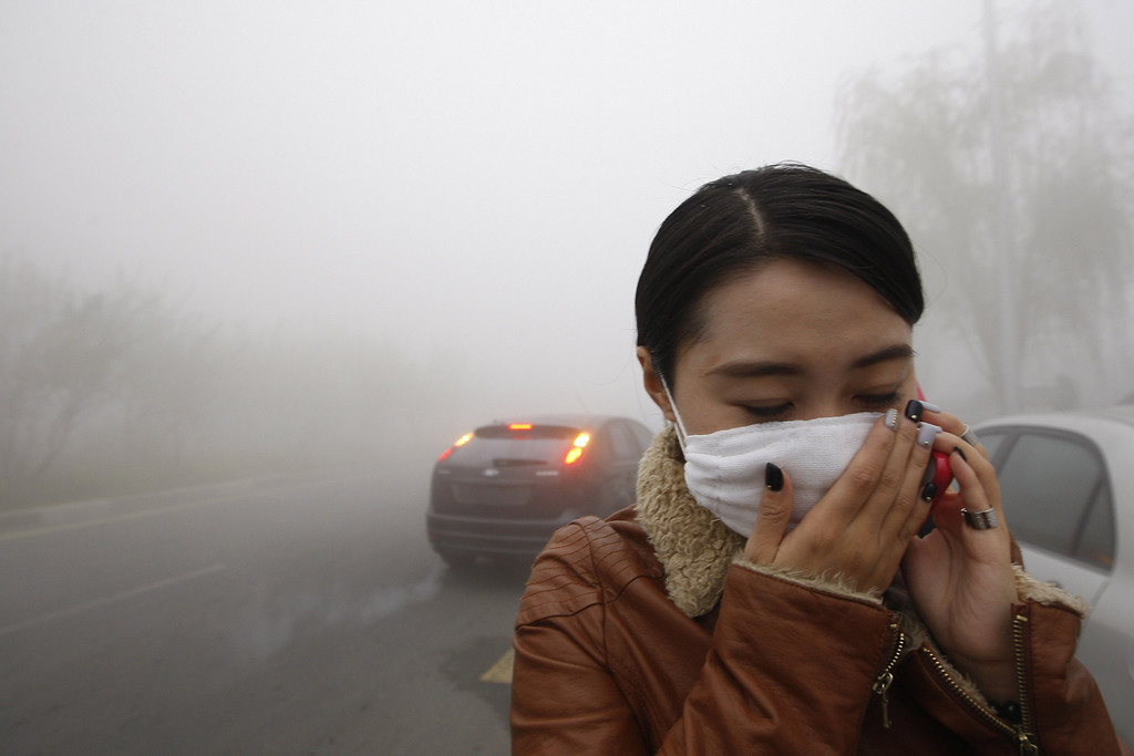 . A woman wearing a mask covers her mouth with her hands as she walks in the smog in Harbin, northeast China\'s Heilongjiang province, on October 21, 2013.    AFP PHOTOSTR/AFP/Getty Images