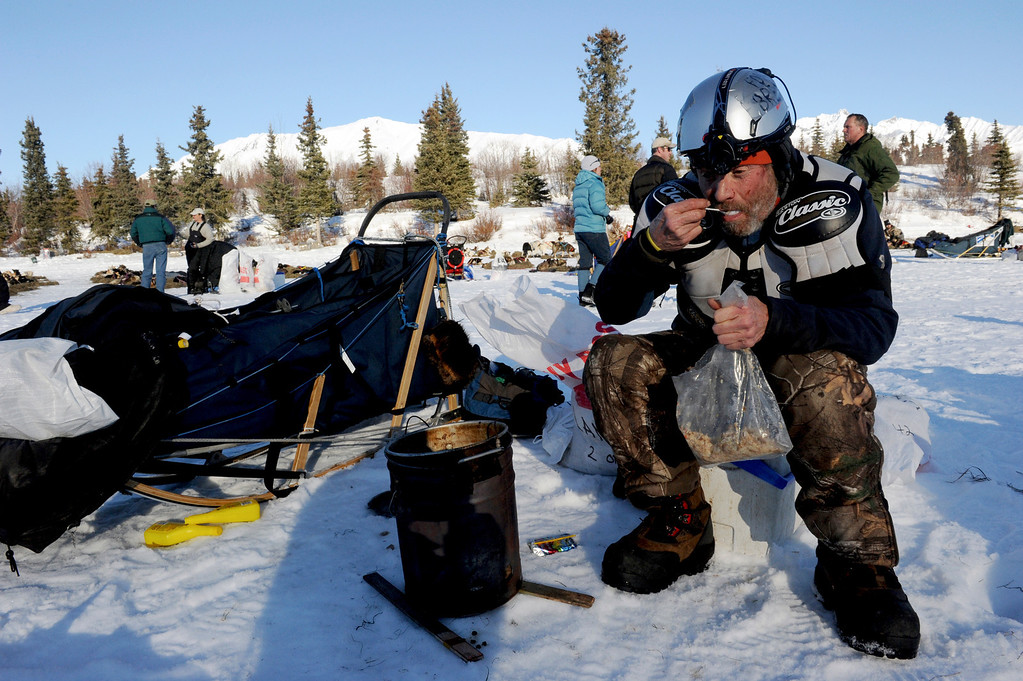 . In this March 3, 2014 photo, Musher Jim Lanier eats his lunch at the Rainy Pass checkpoint during the 2014 Iditarod Trail Sled Dog Race near Puntilla Lake, Alaska. (AP Photo/The Anchorage Daily News, Bob Hallinen)