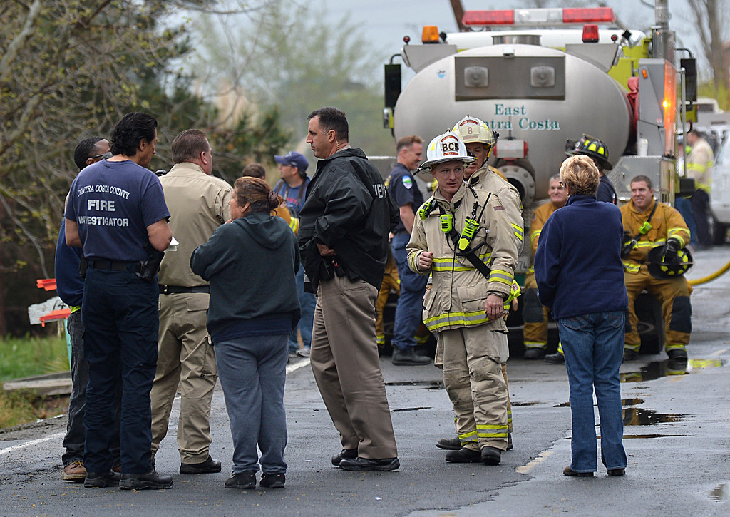 . Fire investigators gather on Taylor Road in Bethel Island, and talk to homeowners after a two-alarm fire  in Bethel Island, Calif., on Wednesday, March 20, 2013. The blaze, which started in a one-story home, destroyed two homes and damaged a third. (Dan Rosenstrauch/Staff)