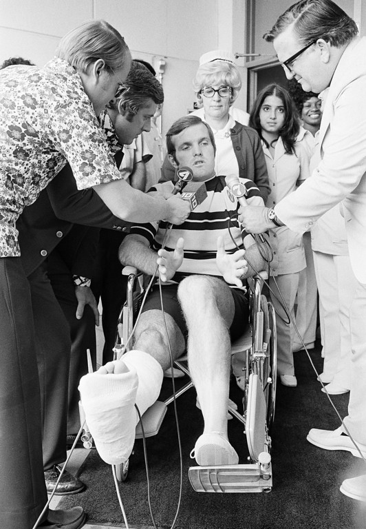 . With mike cords draped over his fractured leg a dislocated ankle, Miami Dolphin quarterback Bob Griese gestures as he tells newsmen Monday, Oct. 17, 1972 in Miami, how was tackled in Sunday\'s game with San Diego that resulted in the injuries. Griese left Miami\'s Mercy Hospital on Monday. (AP Photo/Jim Bourdier)