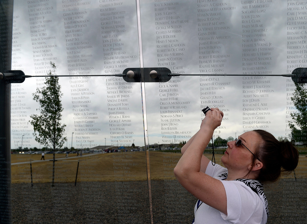 . Kim Thout, 37, takes a photo of her great uncle\'s name on the glass after the dedication. (Photo By John Leyba/The Denver Post)