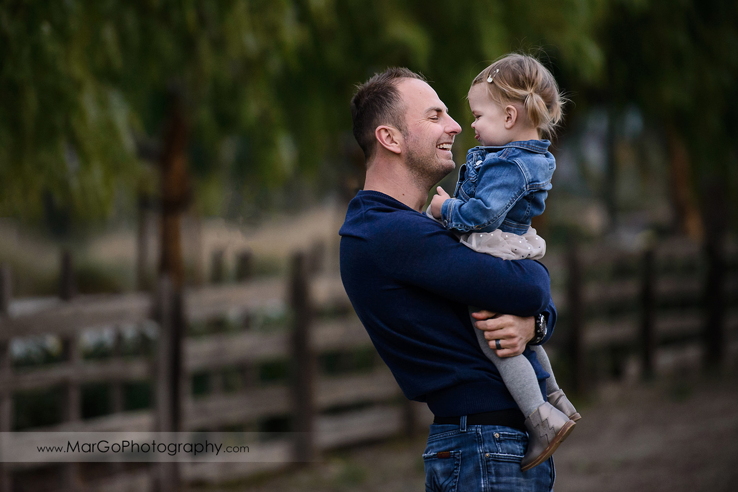 portrait of father wearing navy blue sweater holding little girl in white dress and jeans jacket during family session at San Jose Martial Cottle Park