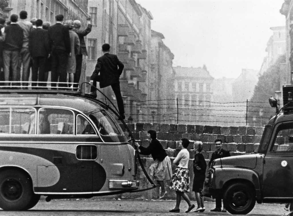 . Sightseers climb onto a bus to look at the newly-built Berlin Wall.   (Photo by Keystone/Getty Images)