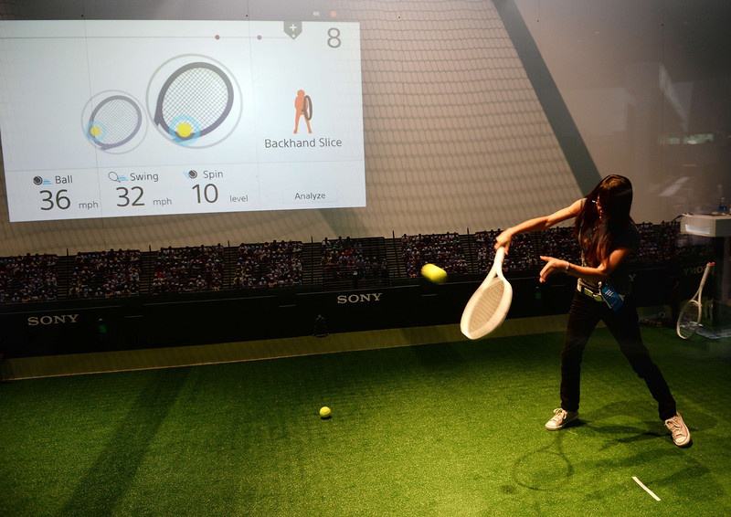 . An attendee hits balls with a Sony bluetooth tennis racket, while his real-time statistics are seen on the screen at right, on the final day of the 2014 International Consumer Electronics Show (CES) on January 10, 2014 in Las Vegas, Nevada. The prototype racket is equipped with vibration and motion sensors which collect information about the player\'s swing speed, ball speed and spin rate and relay it to a Smartphone or tablet. (Robyn Beck/AFP/Getty Images)