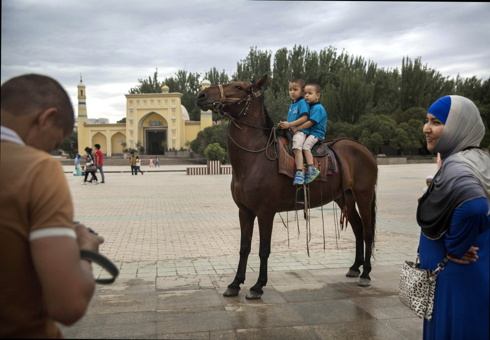 . KASHGAR, CHINA - JULY 31: Uyghur boys sit on top of a horse to have their picture taken in front of the Id Kah Mosque, China\'s largest mosque, on July 31, 2014 in Kashgar, Xinjiang Province, China.   The imam of the Id Kah mosque has been stabbed to death, media reports say. Jume Tahir, 74, was allegedly  leaving the mosque early Wednesday morning following prayers when he was attacked by assailiants.   (Photo by Getty Images/Getty Images)