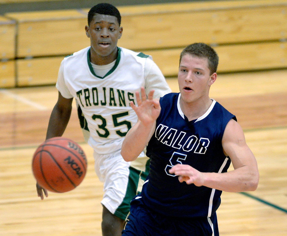 . Eagles\' senior guard Christian McCaffrey (5) moved the ball ahead of Trojans\' defender Marquise Johnson (35) in the second half. The Valor Christian High School boy\'s basketball team defeated Aurora Central 60-52 Wednesday night, January 8, 2014. Photo By Karl Gehring/The Denver Post