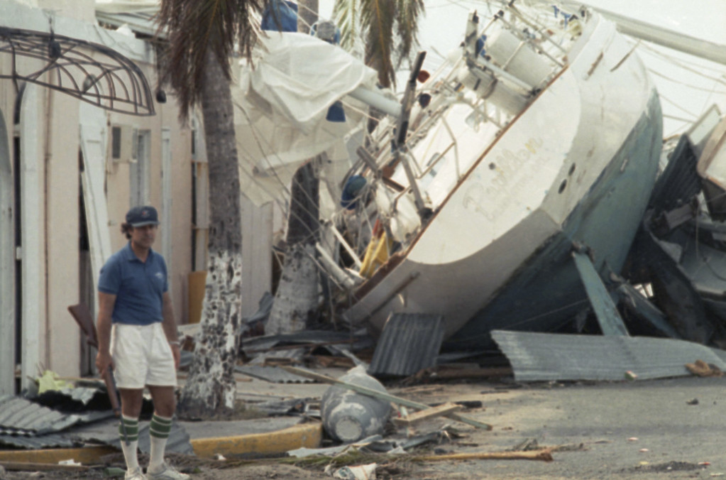 . Sid Kalmas stands guard over his hotel after the Caribbean area was swept by Hurricane Hugo, Sept. 20, 1989, Christiansted, U.S. Virgin Islands. The yacht in background was dumped there by Hugo, which proceeded to cause massive damage in South Carolina when it hit the mainland. (AP Photo/Steve Helber)