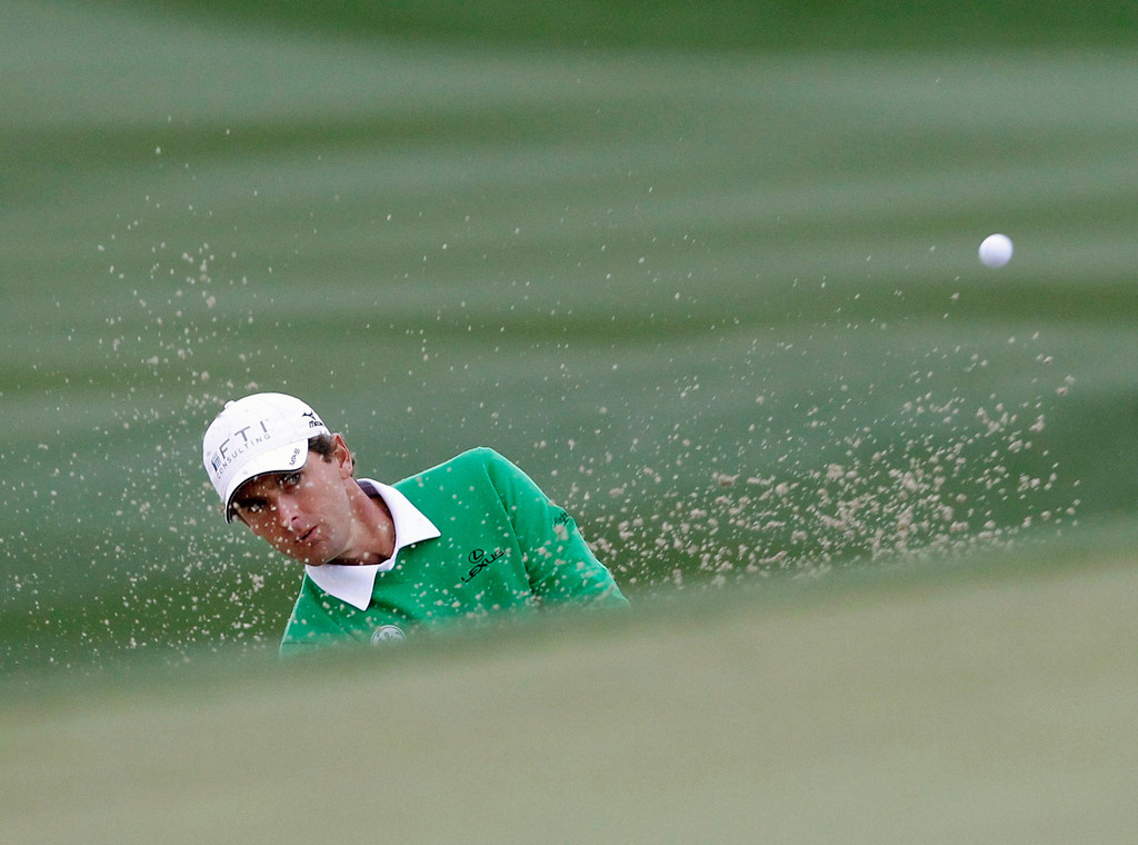 . Charles Howell III of the U.S. hits from the sand onto the 13th green against Tiger Woods of the U.S. during the weather delayed first round of the WGC-Accenture Match Play Championship golf tournament in Marana, Arizona February 21, 2013. REUTERS/Matt Sullivan