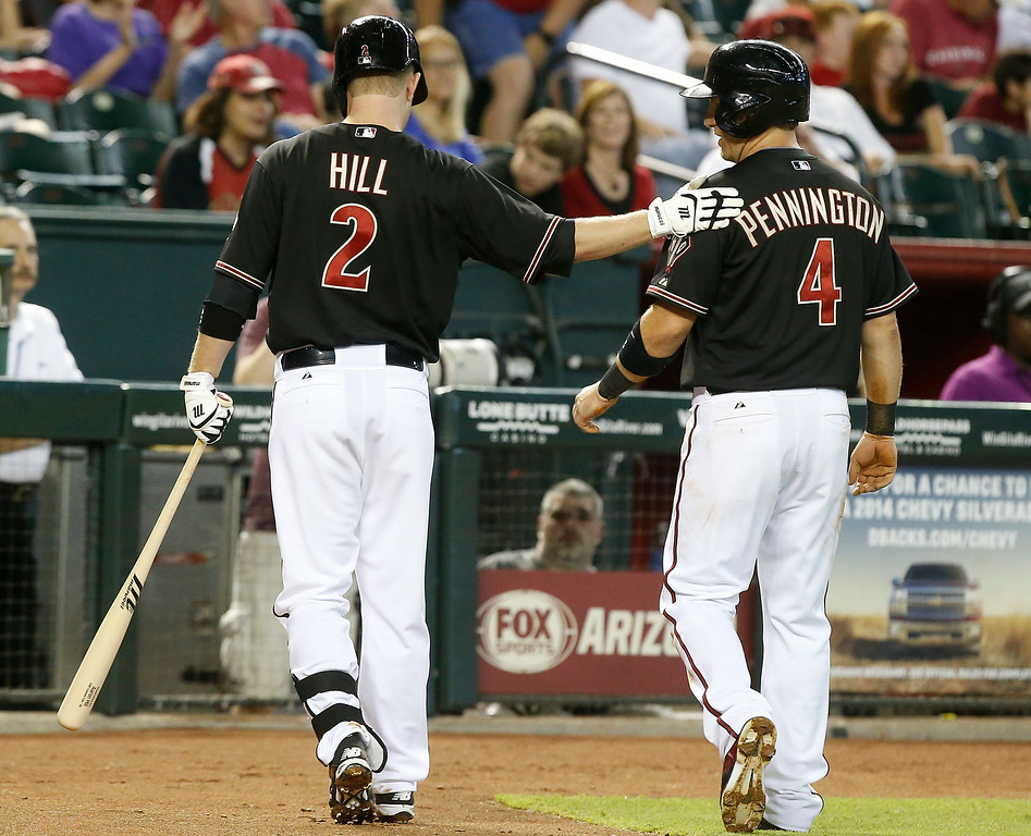 . Arizona Diamondbacks\' Aaron Hill gives teammate Cliff Pennington a pat on the back after scoring the Diamondbacks first run against the Colorado Rockies in the first inning during a baseball game, Saturday, Aug. 9, 2014, in Phoenix. (AP Photo/Darryl Webb)