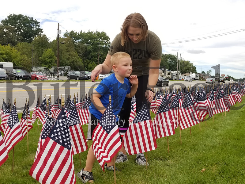 Megan Klingensmith helps her son, Grady, place one flag in a memorial of 660 that represents the total number of veterans who die by suicide each month.