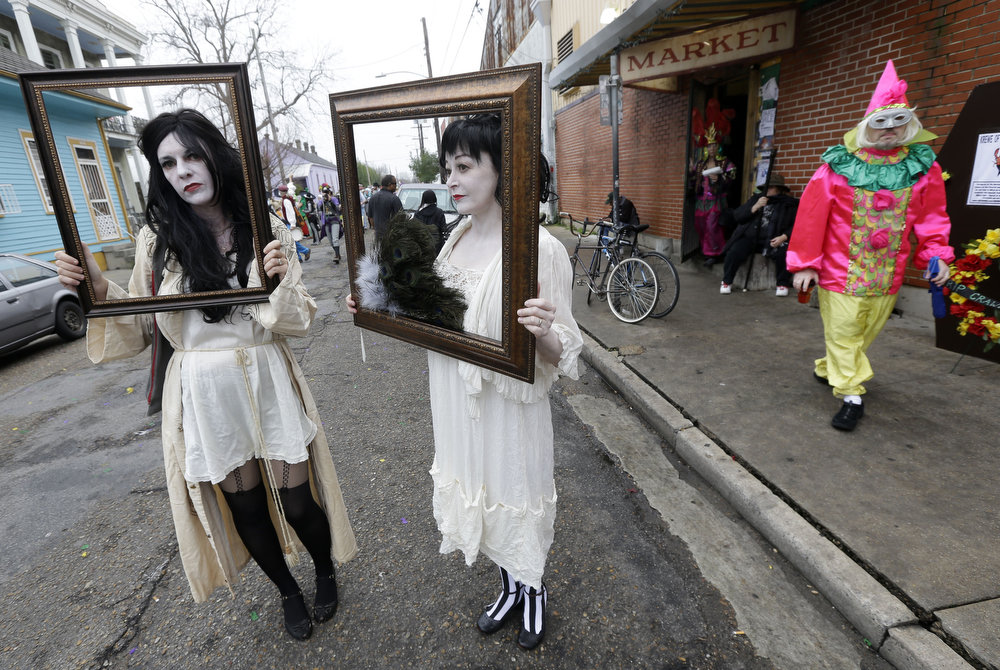 Description of . Babbette Hines, left, and Carol Jean Dixon, both of New Orleans, pose with their costumes representing sad ladies of the night, inspired by Storyville photographer E.J. Bellocq, before the start of the Society of Saint Anne walking parade in the Bywater section of New Orleans during Mardi Gras day, Tuesday, Feb. 12, 2013. (AP Photo/Gerald Herbert)