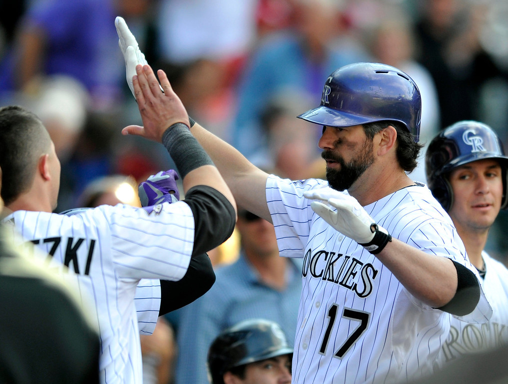 . Colorado Rockies\' Todd Helton (17) is congratulated by teammates after hitting a solo home run off St. Louis Cardinals relief pitcher Edward Mujica during the ninth inning of a baseball game on Thursday, Sept. 19, 2013, in Denver. (AP Photo/Jack Dempsey)