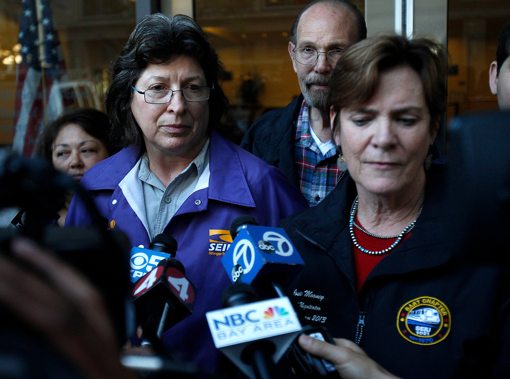 . Roxanne Sanchez, president of SEIU 1021, left, standing next Josie Mooney, lead negotiator of Service Employees International Union local 1021, right, speaks to the media outside of the Caltrans offices in downtown Oakland, Calif. on Sunday, Aug. 11, 2013.  (Nhat V. Meyer/Bay Area News Group)