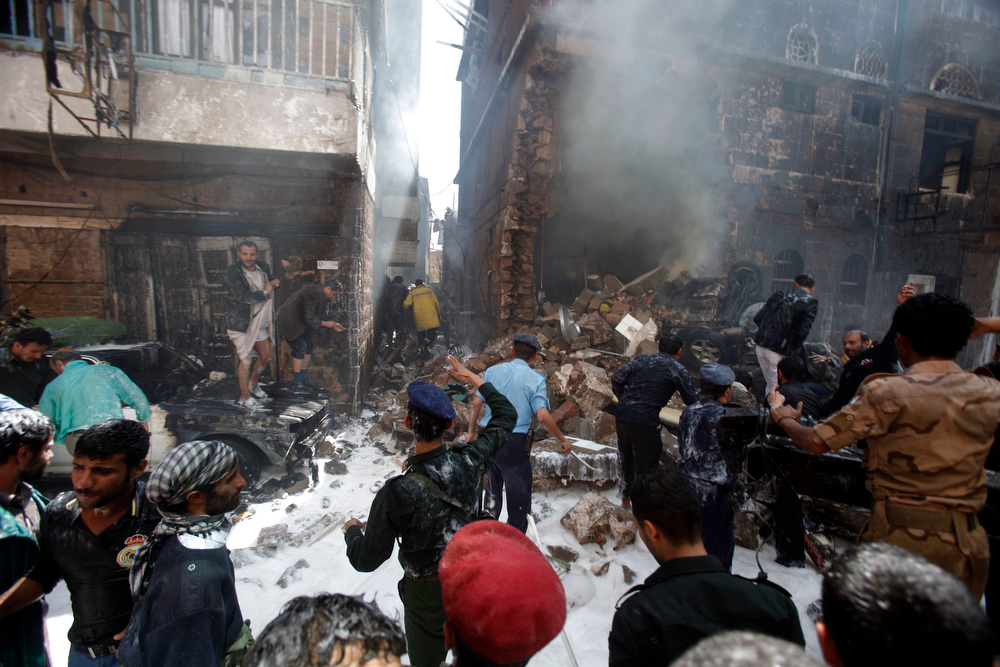 . Military personnel and people search through the wreckage at the site of a military aircraft crash in Sanaa February 19, 2013. A Yemeni air force plane crashed in the centre of the capital Sanaa on Tuesday, killing at least 11 people and wounding 15, security sources said. REUTERS/Khaled Abdullah