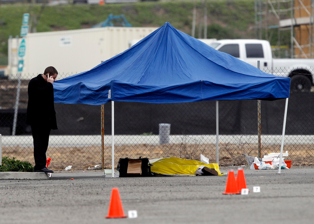 . A police officer makes a call next to the body of a man in the parking lot of a computer store, after he was shot while returning to his vehicle, in Tustin, California, February 19, 2013. A gunman on a shooting rampage in southern California killed three people on Tuesday in an attack at a home and three carjackings, before killing himself with a shotgun as officers closed in, police said. REUTERS/Alex Gallardo