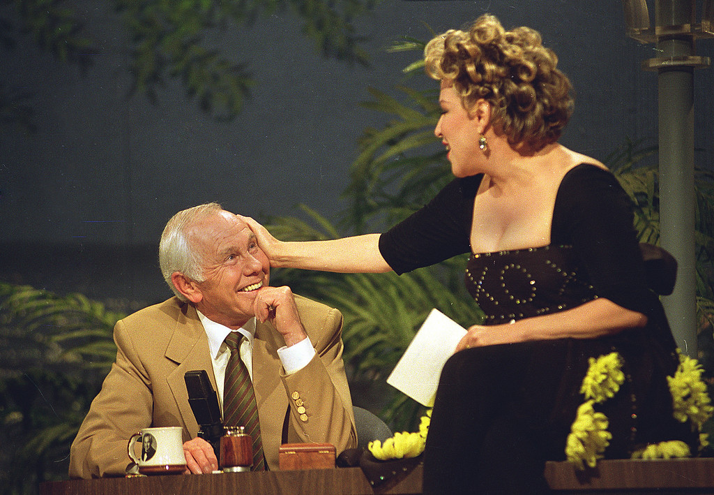 ". Entertainer Bette Midler caresses talk show host Johnny Carson during his next-to-last taping of the ""Tonight Show\"" in Burbank, Ca., Thursday, May 21, 1992.  Carson will retire tomorrow after 30 years of late-night television.  (AP Photo/Douglas C. Pizac)"