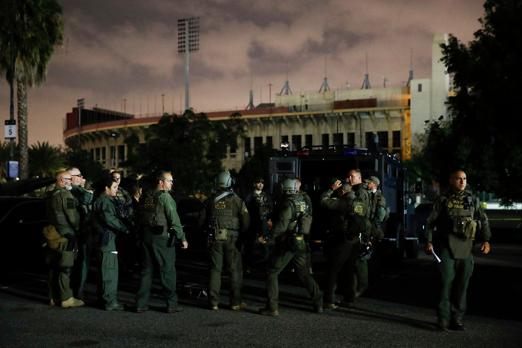 . ATF agents gather for a briefing in the parking lot of the Los Angeles Memorial Coliseum early Wednesday morning, May 17, 2017, in Los Angeles. Hundreds of federal and local law enforcement fanned out across Los Angeles, serving arrest and search warrants as part of a three-year investigation into the violent and brutal street gang MS-13. (AP Photo/Jae C. Hong)