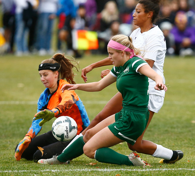 Billings Central's Zoie Althoff (11) attacks the goal while defended by Laurel goalie Mya Hansen (00) and Laurel's Kolby Gibbs (17) in the first half of the Class A state championship match at Wendy's Field at Rocky Mountain College on Saturday, Oct. 27, 2018.