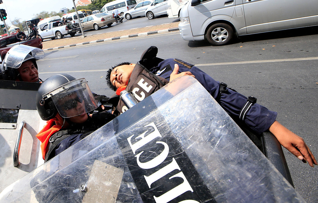 . An injured Thai police is treated by a colleague on the back of a pick up truck during a clash between police force and anti-government protesters Tuesday, Feb. 18, 2014 in Bangkok, Thailand.  (AP Photo/Wason Wanichakorn)