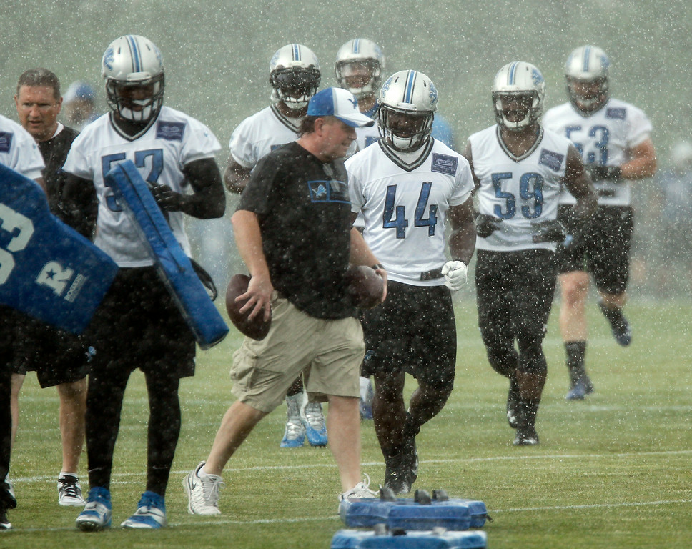 . Detroit Lions linebackers Justin Jackson (44), Tahir Whitehead (59) and Corey Greenwood (53) move to another drill during a downpour on the final day of NFL football minicamp Thursday, June 12, 2014, in Allen Park, Mich. (AP Photo/Duane Burleson)