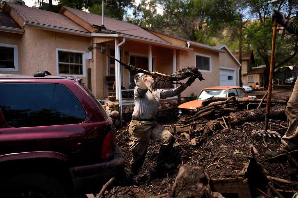. Manitou Springs, CO. - July 02: Alison Canavan with AmeriCorps NCCC clearing the area around a car for a backhoe after a flash flood washed through houses, streets and businesses when a downpour hit the Waldo Canyon burn scar in El Paso County July 02, 2013 Manitou Springs, Colorado. (Photo By Joe Amon/The Denver Post)