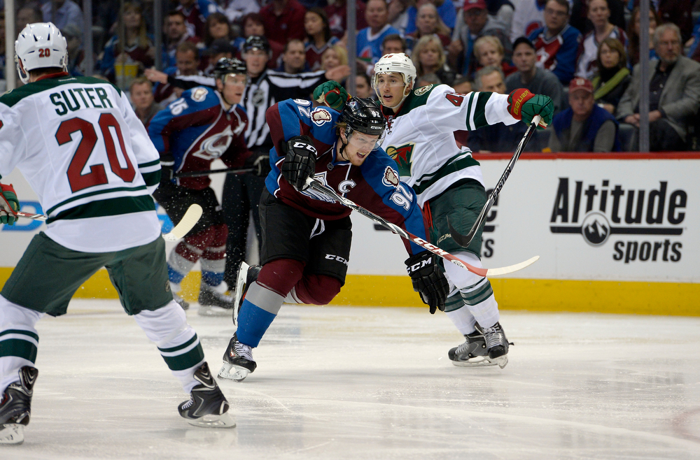 . Gabriel Landeskog (92) of the Colorado Avalanche breaks through traffic and passes Jared Spurgeon (46) and Ryan Suter (20) of the Minnesota Wild during the third period of action. The Colorado Avalanche hosted the Minnesota Wild for the first playoff game at the Pepsi Center on Thursday, April 17, 2014. (Photo by John Leyba/The Denver Post)