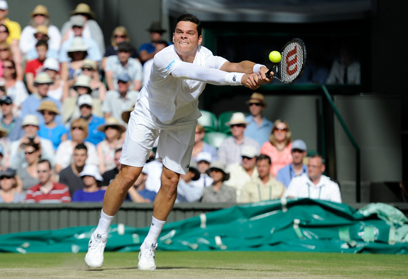 . Milos Raonic of Canada plays a return to Roger Federer of Switzerland during their men�s singles semifinal match at the All England Lawn Tennis Championships at Wimbledon, London, Friday, July, 4, 2014. (AP Photo/Facundo Arrizabalaga, Pool)