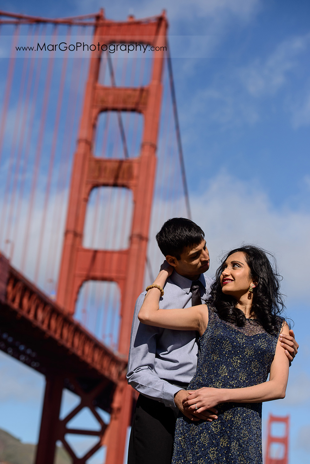 portrait of Indian couple in blue clothes with San Francisco Golden Gate Bridge in the background during engagement session