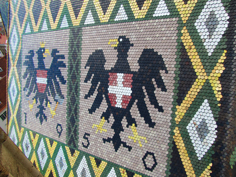 35-On the north side of the tiled roof are the coats of arms of the City of Vienna and of the Republic of Austria. The retiling of the burned and reconstructed roof was completed in 1950.