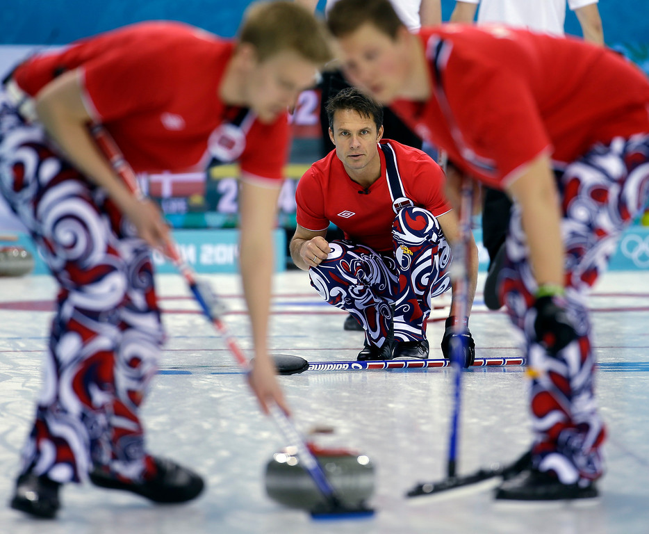 . Norway\'s Thomas Ulsrud delivers the rock to his sweepers during a round robin match against Denmark at the 2014 Winter Olympics, Monday, Feb. 17, 2014, in Sochi, Russia. (AP Photo/Morry Gash)
