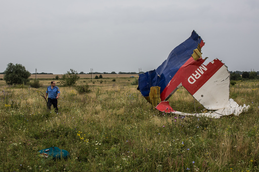 . A Ukrainian police officer searches for human remains found in a field on July 18, 2014 in Grabovka, Ukraine. Air Malaysia flight MH17 travelling from Amsterdam to Kuala Lumpur crashed yesterday on the Ukraine/Russia border near the town of Shaktersk. The Boeing 777 was carrying 298 people including crew members, the majority of the passengers being Dutch nationals, believed to be at least 173, 44 Malaysians, 27 Australians, 12 Indonesians and 9 Britons.  (Photo by Brendan Hoffman/Getty Images)