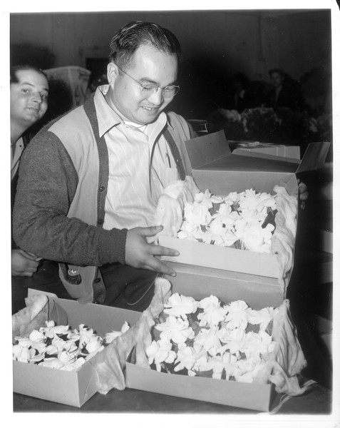 """""""George Inagaki (Nisei), Executive-Secretary of the South District Council of the Japanese-American Citizens' League, is manager of the Kitagawa Nursery.  He is shown selling gardenias at the Los Angeles wholesale flower market.""""--caption on photograph"""