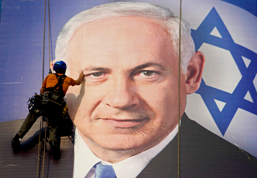 Description of . A worker hangs a huge poster with an image of Israel's Prime Minister Benjamin Netanyahu overlooking the Ayalon freeway in Tel Aviv, Israel on Thursday, Jan. 17, 2013. After a lackluster three-month campaign, there seems to be little doubt that Prime Minister Benjamin Netanyahu is on his way to re-election. But the makeup of Netanyahu's next government remains a matter of great uncertainty. (AP Photo/Ariel Schalit, File)
