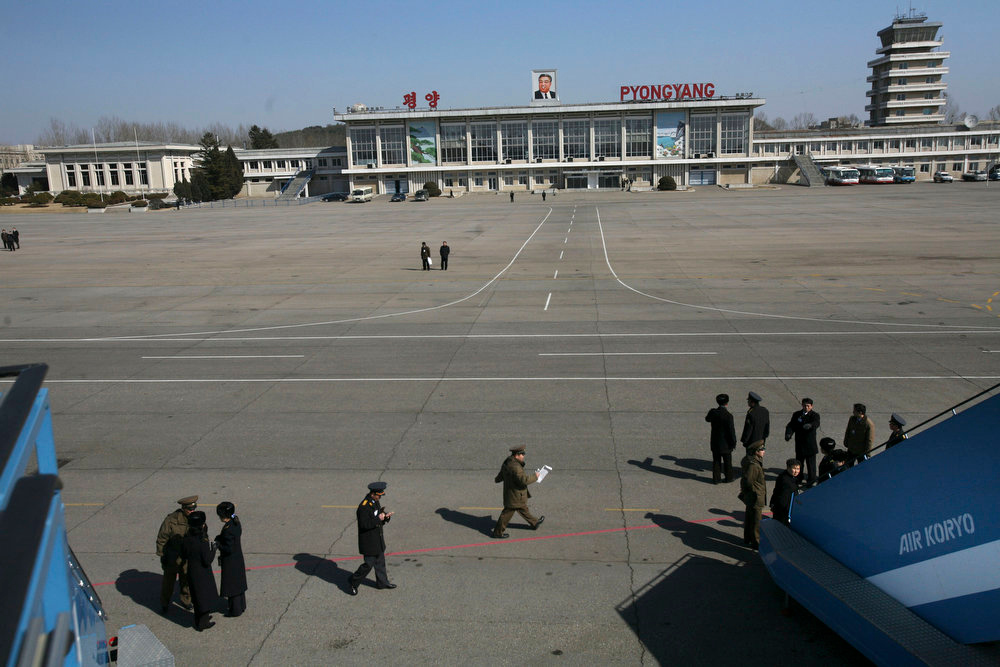 Description of . North Korean officials stand on the tarmac next to Air Koryo airplane stairs in front of the Pyongyang airport in Pyongyang, North Korea on Feb. 27, 2008. Air Koryo jets once traversed the skies of the Eurasian landmass, linking communist North Korea with airports in Cold War capitals as far afield as Moscow, Prague and the former East Berlin. Nowadays, the aging Russian-built craft of the rickety state airline mostly ply routes close to home, with flights beyond nearby Chinese cities and Russia's Far East extremely rare.  (AP Photo/David Guttenfelder)
