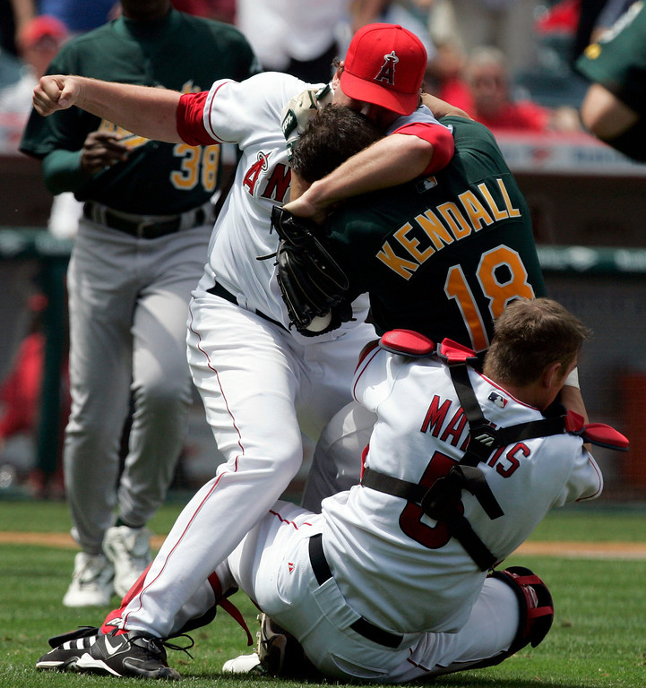 . Los Angeles Angels starting pitcher John Lackey, left, and catcher Jeff Mathis, right, brawl with Oakland Athletics\' Jason Kendall after Kendell rushed the mound during the sixth inning of their baseball game, Tuesday, May 2, 2006, in Anaheim, Calif. (AP Photo/Chris Carlson)