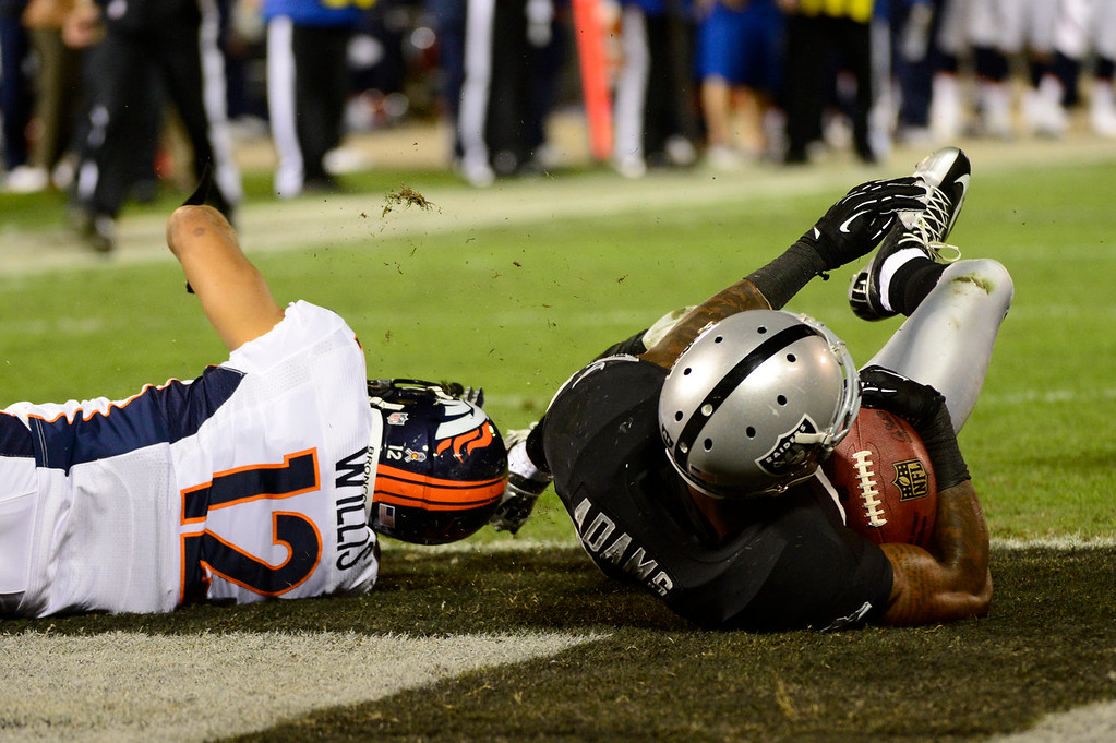 . Oakland Raiders defensive back Phillip Adams #28 intercepts an under thrown ball in front of Denver Broncos wide receiver Matt Willis #12 in the end zone in the first half at the O.co Coliseum, in Oakland , CA December 06, 2012.      Joe Amon, The Denver Post