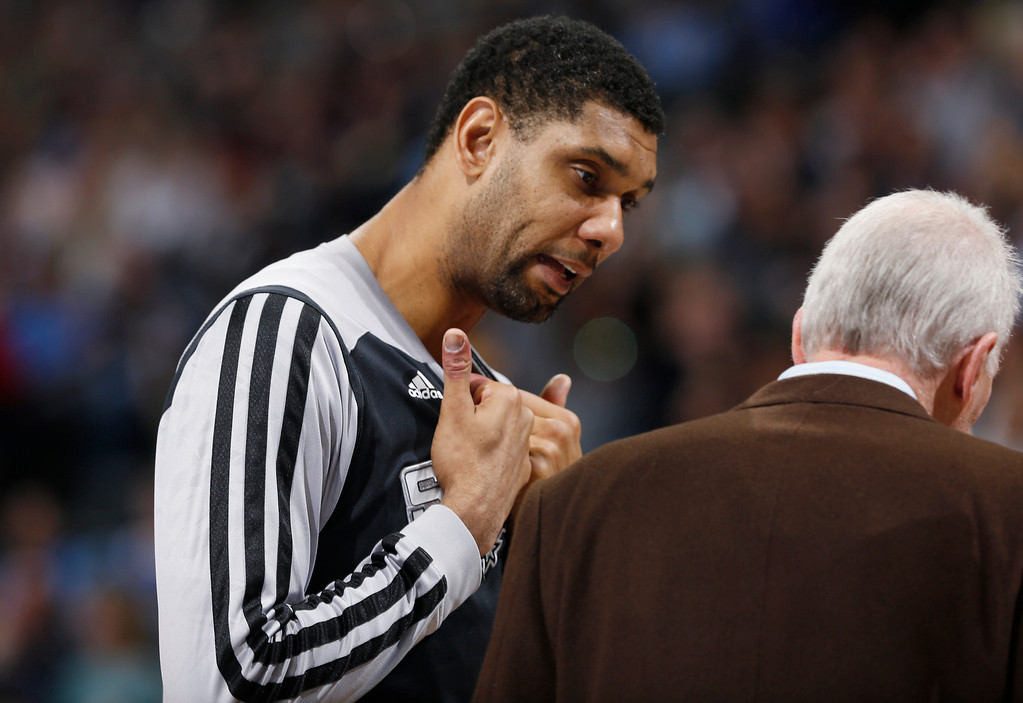 . San Antonio Spurs center Tim Duncan, left, confers with coach Gregg Popovich during a timeout against the Denver Nuggets in the fourth quarter of the Spurs\' 133-102 victory in an NBA basketball game in Denver on Friday, March 28, 2014. (AP Photo/David Zalubowski)