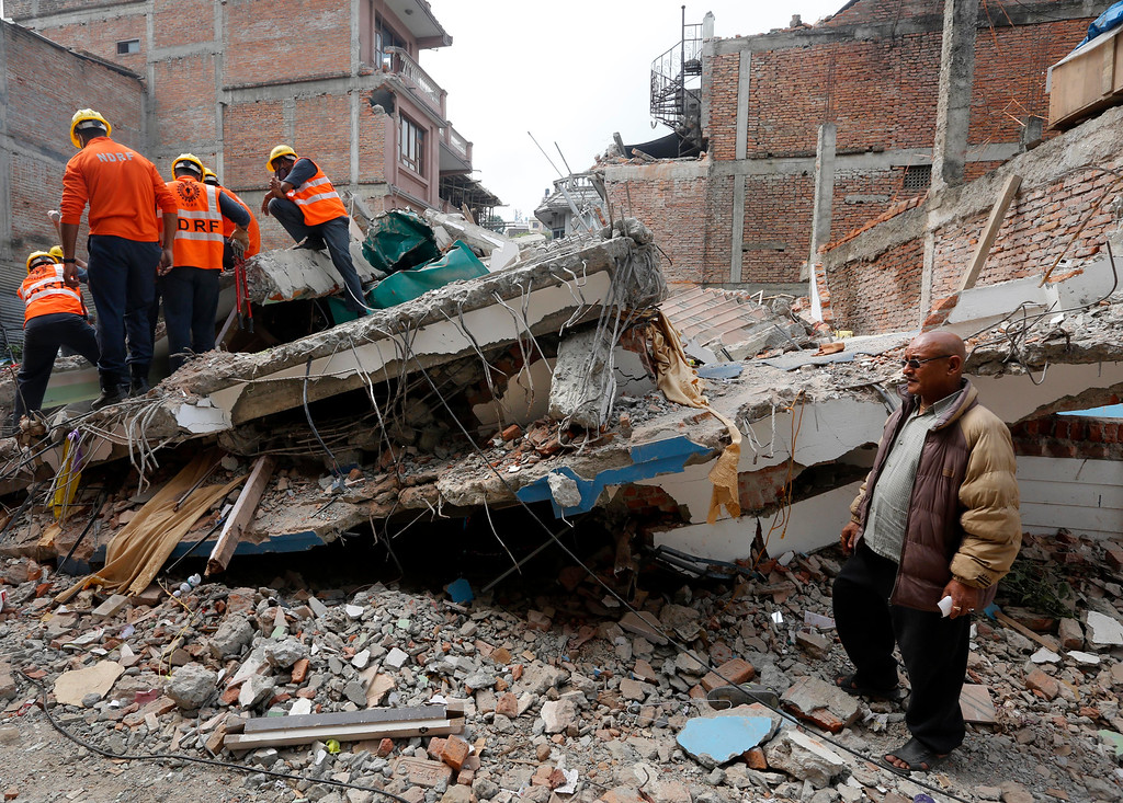 . In this Tuesday, April 28, 2015 photo, Bharatman Pradhan, right, stands near his house collapsed in Saturday\'s massive earthquake as Indian rescue workers search for his family members in Kathmandu, Nepal. When the quake crumpled his four-story house into a cloud of dust April 25, a total of 18 family members were killed in the building. About 30 of relatives had gathered in the house for a weeklong traditional Hindu prayer session. At 11:56 a.m., the house began shaking. About a dozen people had managed to flee in time. (AP Photo/Manish Swarup)