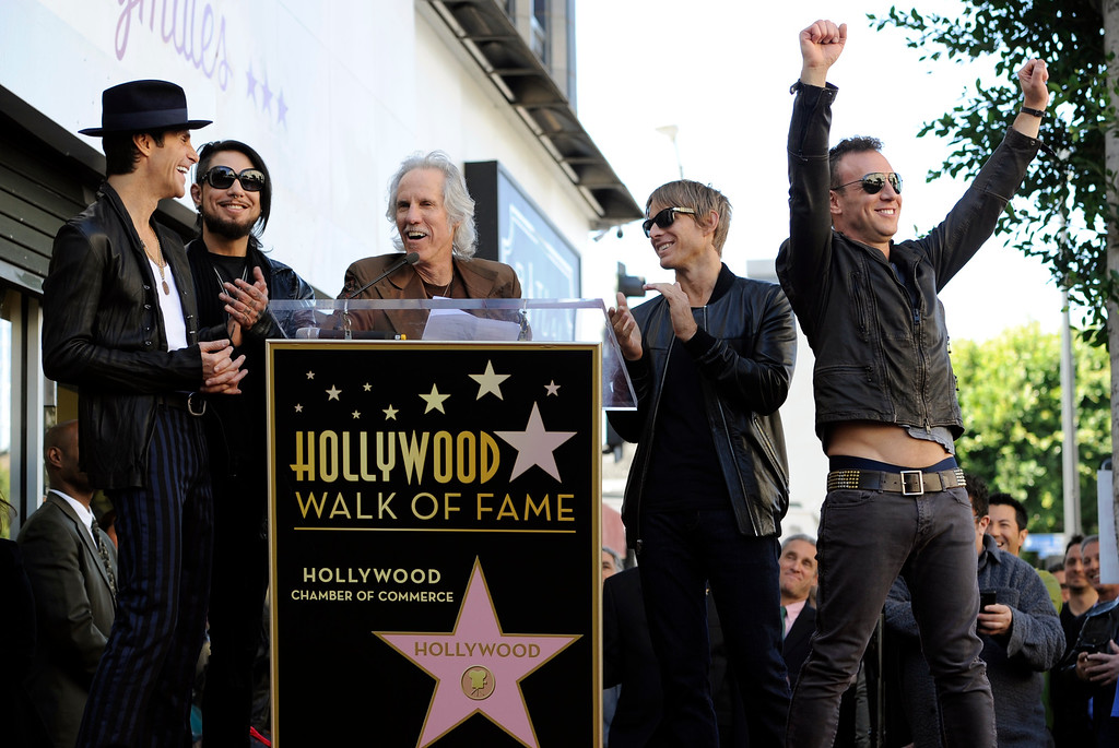 . John Densmore of The Doors, center, pays tribute to Jane\'s Addiction band members, left to right, Perry Farrell, Dave Navarro, Chris Chaney and Stephen Perkins during a ceremony to award the band a star on the Hollywood Walk of Fame on Wednesday, Oct. 30, 2013, in Los Angeles. (Photo by Chris Pizzello/Invision/AP)