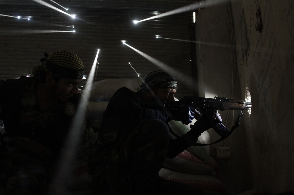 . Two Syrian rebels take sniper positions at the heavily contested neighborhood of Karmal Jabl in central Aleppo on October 18, 2012. Violence persisted on October 19 with rebels and loyalists of President Bashar al-Assad locked in battle for the northwestern town of Maaret al-Numan on the Damascus-Aleppo highway linking Syria\'s two biggest cities. (Javier Manzano/AFP/Getty Images)