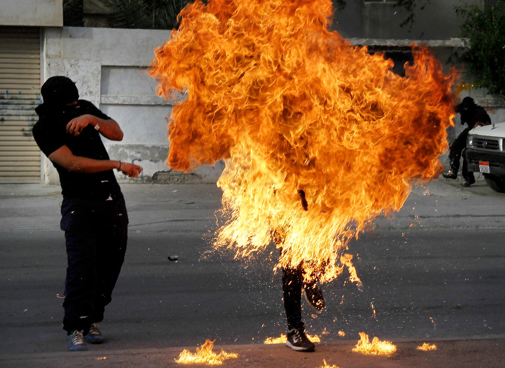 """. A Bahraini anti-government protester is engulfed in flames when a shot fired by riot police hit the petrol bomb in his hand that he was preparing to throw during clashes in Sanabis, Bahrain, Thursday, March 14, 2013. Protests and clashes erupted in opposition areas nationwide with government opponents observing a \""""Dignity Strike\"""" blocking roads, closing shops, protesting and staying home from work and school called by the more radical February 14 youth group. (AP Photo/Hasan Jamali)"""