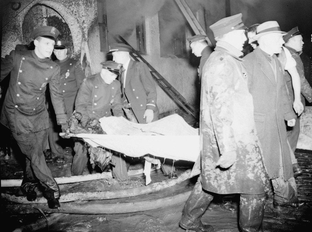 . Police remove the burned body of a victim of a sudden fire that swept the Cocoanut Grove Night Club in Boston, Ma., the night of November 28, 1942, during the height of a football weekend of merrymaking.  The fire, which spread with lightning speed through the club, killed 492 persons.  (AP Photo)
