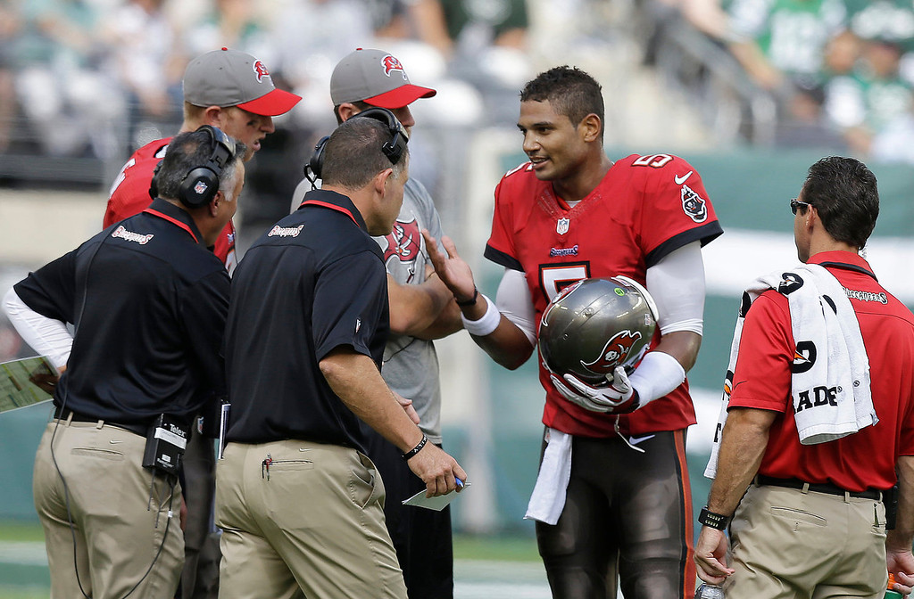 . Tampa Bay Buccaneers quarterback Josh Freeman, center right, talks to coach Greg Schiano, second from left in foreground, in the first half of an NFL football game against the New York Jets, Sunday, Sept. 8, 2013, in East Rutherford, N.J. (AP Photo/Mel Evans)